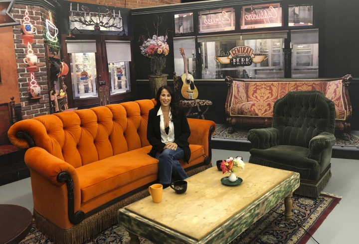 "This Sept. 5, 2019 photo shows actress Maggie Wheeler, who played Janice on the NBC sitcom ""Friends,"" posing in a replica of the Central Perk set, at the New York City Pop-Up experience in New York. There are different sections to walk through in 8,500 square feet of loft space, where more than 50 original props from the show are on display. The popular comedy is celebrating its 25th anniversary this year. (AP Photo/Brooke Lefferts)"