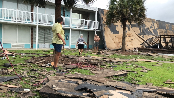 Residents of the Bogue Shores condominiums work to hook up a generator after the complex lost its roof during high winds from Hurricane Dorian in Atlantic Beach, N.C., on Friday, Sept. 6, 2019. Only a few residents stayed behind after an evacuation order and no one was injured. (AP Photo/Jeffrey Collins)