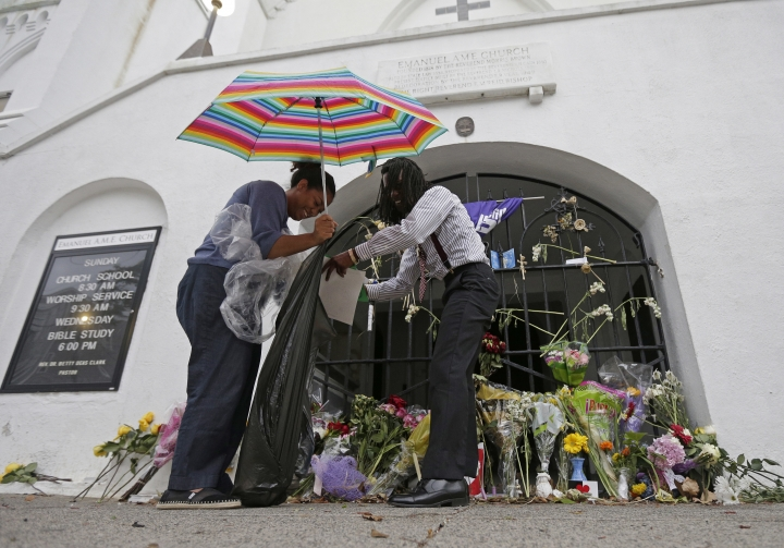 FILE - In this June 17, 2016, file photo Barrye Browne, left, and Daron Calhoun collect memorials placed at Mother Emanuel AME Church in Charleston, S.C., on the anniversary of the killing of nine black parishioners during bible study. The gunman who killed the worshippers had been arrested on drug charges just weeks earlier. Although that arrest should have prevented him from purchasing the pistol he used in the attack, the examiner reviewing the sale never saw the arrest report because the wrong agency was listed in state criminal history records. (AP Photo/Chuck Burton, File)