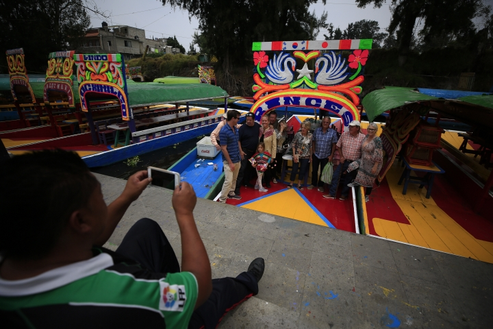 A gondolier takes a photo for a group of Americans after they took a ride on a trajinera, colorful passenger boats typically rented by tourists, families, and groups of young people, in Xochimilco, Mexico City, Friday, Sept. 6, 2019. The usually festive Nativitas pier was subdued and largely empty Friday afternoon, with some boat operators and vendors estimating that business was down by 80% on the first weekend following the drowning death of a youth that was captured on cellphone video and seen widely in Mexico. Borough officials stood on the pier to inform visitors of new regulations that went into effect Friday limiting the consumption of alcohol, prohibiting the use of speakers and instructing visitors to remain seated.(AP Photo/Rebecca Blackwell)