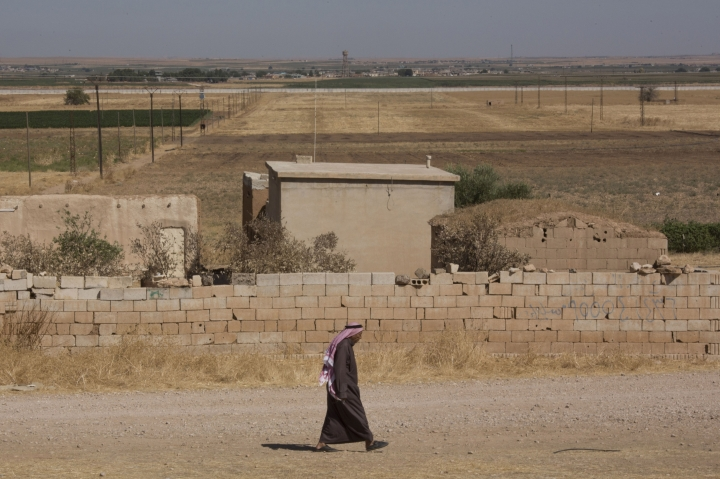 "A man walks near a road where Turkish and American forces are conducting their first joint ground patrol in the so-called ""safe zone"" on the Syrian side of the border with Turkey, seen in the background, near Tal Abyad, Syria, Sunday, Sept. 8, 2019. Turkey hopes the buffer zone, which it says should be at least 30 kilometers (19 miles) deep, will keep Syrian Kurdish fighters, considered a threat by Turkey but U.S. allies in the fight against the Islamic State group, away from its border. (AP Photo/Maya Alleruzzo)"
