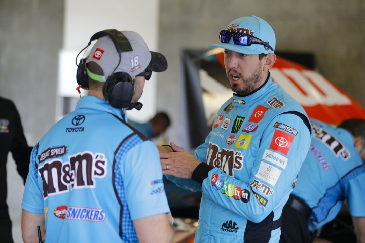 NASCAR driver Kyle Busch talks with a member of his crew after he qualified the NASCAR Brickyard 400 auto race at the Indianapolis Motor Speedway, Sunday, Sept. 8, 2019, in Indianapolis. (AP Photo/Darron Cummings)