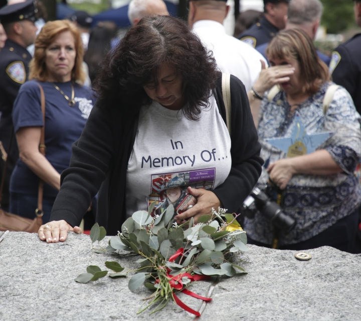 FILE- In this May 30, 2019 file photo, Tina Tilearcio pauses at a stone that is part of the new 9/11 Memorial Glade on the grounds of the National September 11 Memorial & Museum, after its dedication ceremony in New York. Her husband, Robert Tilearcio, died in 2017 of illness related to his recovery work at ground zero. When nearly 3,000 Sept. 11 victims' names are read aloud on the memorial plaza on Sept. 11, 2019, a half-dozen stacks of stone will quietly salute an untold number of people who aren't on the list. (AP Photo/Seth Wenig)