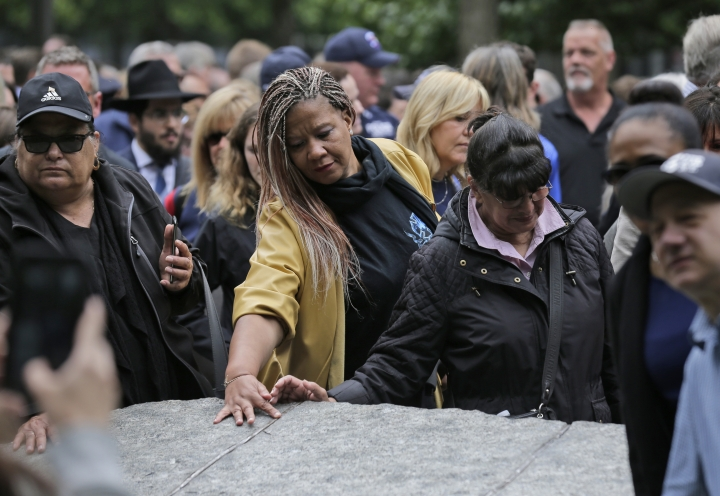 FILE- In this May 30, 2019 file photo, people gather around stones that are part of the new 9/11 Memorial Glade, on the grounds of the National September 11 Memorial and Museum in New York. On Sept. 11, 2019, when nearly 3,000 9/11 victims' names are read aloud on the memorial plaza, the half-dozen stacks of stone of the 9/11 Memorial Glade will quietly salute an untold number of people who aren't on the list. (AP Photo/Seth Wenig, File)