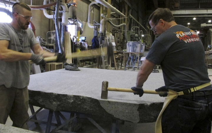 FILE- In this Jan. 8, 2019 file photo, stone cutters Evan Ladd, left, and Andy Hebert cut a piece of granite at Rock of Ages in Barre, Vt., for use in the 9/11 Memorial Glade in New York. Set in a glade of trees at the Nationals September 11 Memorial & Museum, the granite slabs recognize an initially unseen toll of the 2001 terror attacks: firefighters, police and others who died or fell ill after exposure to toxins unleashed in the wreckage. (AP Photo/Lisa Rathke, File)