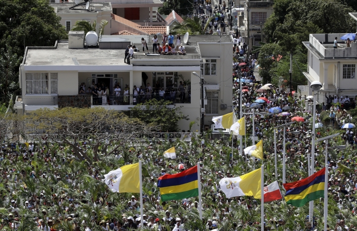 People gather in the streets and stand on rooftops to attend a Mass celebrated by Pope Francis at the Monument Mary Queen of Peace, in Port Louis, Mauritius, Monday, Sept. 9, 2019. Francis has arrived in the Indian Ocean nation of Mauritius to celebrate its diversity, encourage its ethical development and honor a 19th century French missionary who ministered to freed slaves. (AP Photo/Alessandra Tarantino)