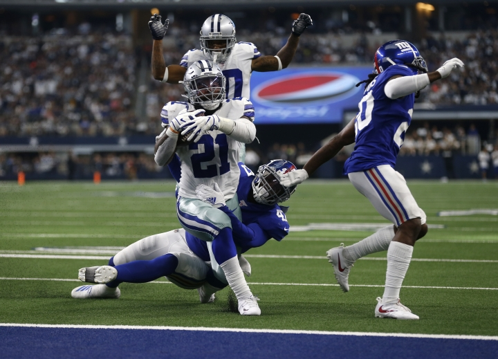 Dallas Cowboys running back Ezekiel Elliott (21) runs the ball for a touchdown after getting past New York Giants outside linebacker Alec Ogletree, center bottom, and Janoris Jenkins, right, as wide receiver Tavon Austin, rear, looks on in the second half of a NFL football game in Arlington, Texas, Sunday, Sept. 8, 2019. (AP Photo/Ron Jenkins)