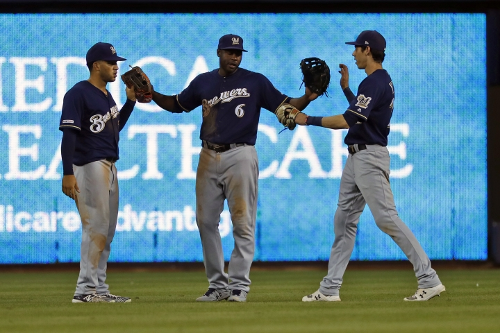 Milwaukee Brewers' Trent Grisham, left, Lorenzo Cain, center, and Christian Yelich celebrate after they defeated the Miami Marlins in a baseball game, Monday, Sept. 9, 2019, in Miami. (AP Photo/Wilfredo Lee)