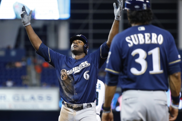 Milwaukee Brewers' Lorenzo Cain (6) celebrates after getting a base hit as first base coach Carlos Subero (31) looks on during the fifth inning of a baseball game against the Miami Marlins, Monday, Sept. 9, 2019, in Miami. (AP Photo/Wilfredo Lee)