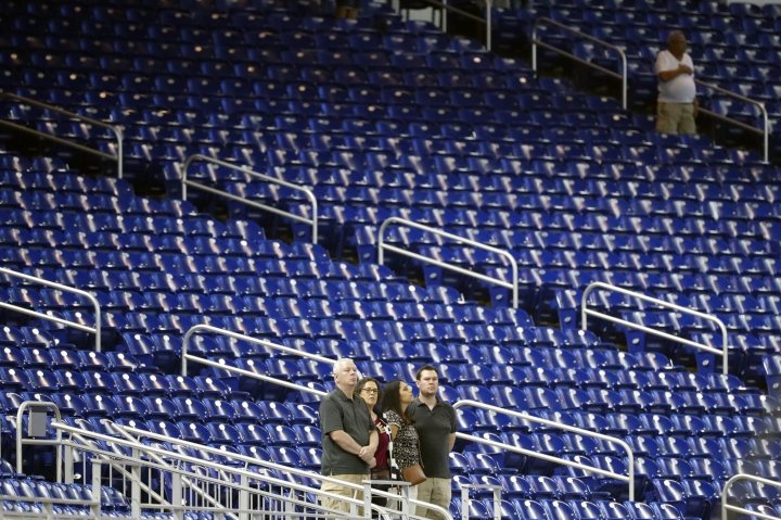 Baseball fans stand among empty seats during the singing of the national anthem before a baseball game between the Miami Marlins and the Milwaukee Brewers, Monday, Sept. 9, 2019, in Miami. (AP Photo/Wilfredo Lee)