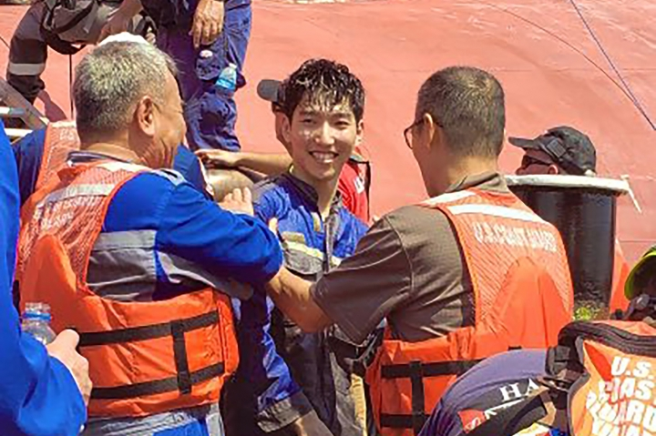 In this image released by the U.S. Coast Guard shows a crew member of the cargo ship Golden Ray as he is helped off the capsized ship Monday, Sept. 9, 2019 off St. Simons Island, Ga. A fire broke out aboard the ship early Sunday, listing it to the side and blocking the shipping channel. (U.S. Coast Guard via AP)