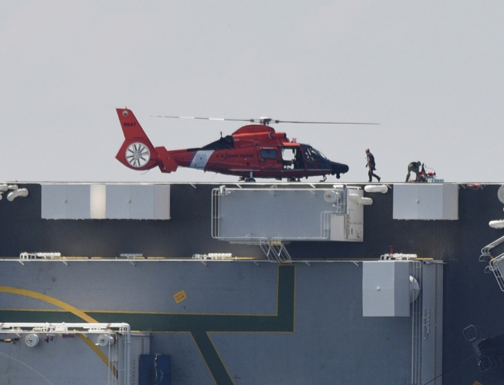 Members of the U.S. Coast Guard unload supplies from a Coast Guard helicopter that landed on the side of the cargo ship Golden Ray, Monday, Sept. 9, 2019, after the vessel overturned while leaving the Port of Brunswick, Ga., early Sunday morning. The Coast Guard were attempting to rescue 4 crew members trapped on the ship. (Bobby Haven/The Brunswick News via AP)