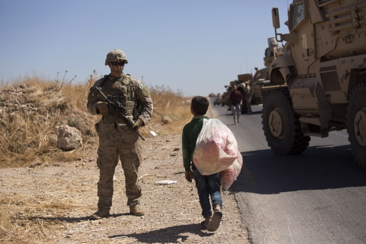 """A Syrian boy selling snacks looks at a U.S. soldier standing guard during the first joint ground patrol by American and Turkish forces in the so-called """"safe zone"""" on the Syrian side of the border with Turkey, near Tal Abyad, Syria, Sunday, Sept. 8, 2019. Turkey hopes the buffer zone, which it says should be at least 30 kilometers (19 miles) deep, will keep Syrian Kurdish fighters away from its border. Turkey considers these Kurdish militias a threat, but they've also been key U.S. allies in the fight against the Islamic State group. (AP Photo/Maya Alleruzzo)"""