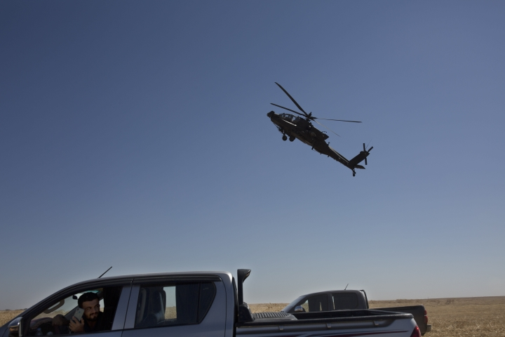 """A helicopter flies low over journalists gathered to film Turkish and American forces on their first joint ground patrol in the so-called """"safe zone"""" on the Syrian side of the border with Turkey, near Tal Abyad, Syria, Sunday, Sept. 8, 2019. Turkey hopes the buffer zone, which it says should be at least 30 kilometers (19 miles) deep, will keep Syrian Kurdish fighters away from its border. Turkey considers these Kurdish militias a threat, but they've also been key U.S. allies in the fight against the Islamic State group. (AP Photo/Maya Alleruzzo)"""