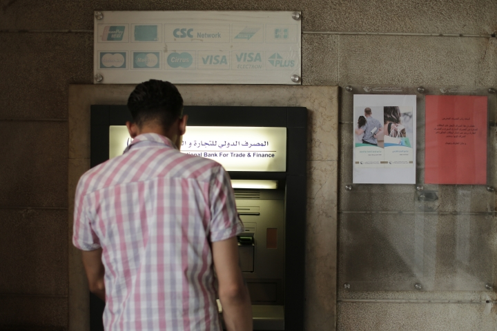 FILE - This July 24, 2019 file photo, a man stands in front of an ATM machine outside a branch of the International Bank for Trade and Finance, in Damascus, Syria. The Syrian pound has crashed to its lowest levels in recent days against the U.S. dollar leading to increase in prices in the war-torn country. The pound was trading Tuesday, Sept. 10, 2019, at 660 to the dollar after it reached 690 pounds last week on the black market, a figure never reached before. (AP Photo/Hussein Malla, File)