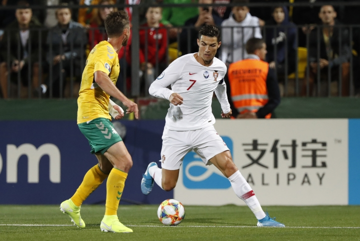 Portugal's Cristiano Ronaldo, right, is challenged by Lithuania's Saulius Mikoliunas during the Euro 2020 group B qualifying soccer match between Lithuania and Portugal at LFF stadium in Vilnius, Lithuania, Tuesday, Sept. 10, 2019. (AP Photo/Mindaugas Kulbis)