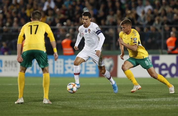 Portugal's Cristiano Ronaldo, center, is challenged by Lithuania's Mantas Kuklys, left and Lithuania's Karolis Laukzemis during the Euro 2020 group B qualifying soccer match between Lithuania and Portugal at LFF stadium in Vilnius, Lithuania, Tuesday, Sept. 10, 2019. (AP Photo/Mindaugas Kulbis)