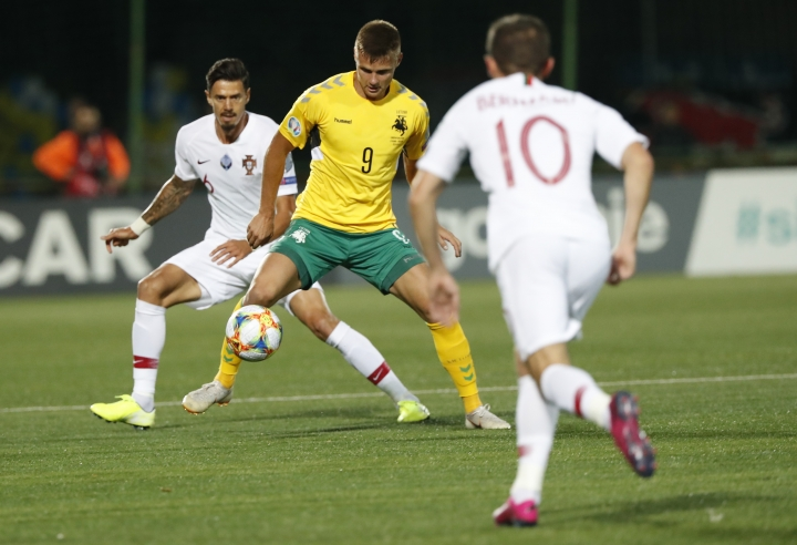 Lithuania's Karolis Laukzemis, center, is challenged by Portugal's Bernardo Silva, right and Portugal's Jose Fonte during the Euro 2020 group B qualifying soccer match between Lithuania and Portugal at LFF stadium in Vilnius, Lithuania, Tuesday, Sept. 10, 2019. (AP Photo/Mindaugas Kulbis)