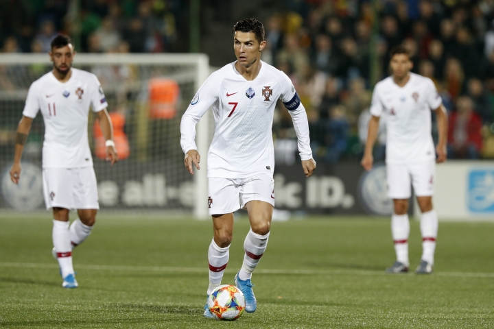 Portugal's Cristiano Ronaldo, center, controls the ball during the Euro 2020 group B qualifying soccer match between Lithuania and Portugal at LFF stadium in Vilnius, Lithuania, Tuesday, Sept. 10, 2019. (AP Photo/Mindaugas Kulbis)