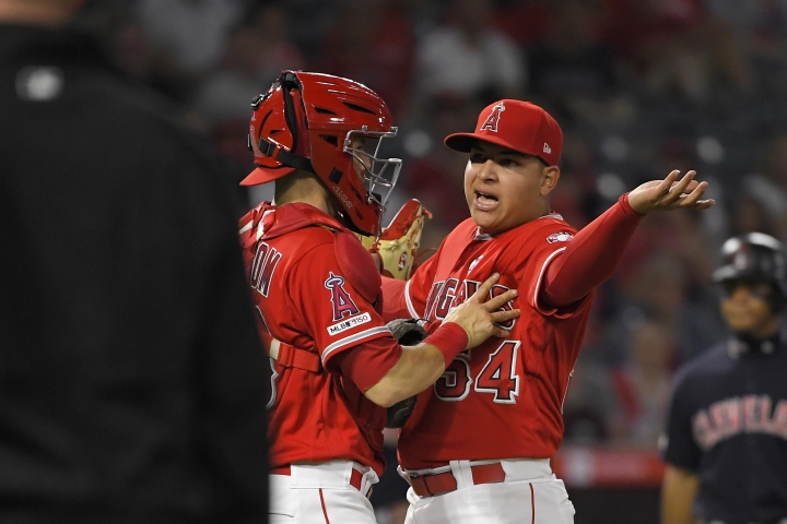 Los Angeles Angels' Jose Suarez, right, is held back by catcher Anthony Bemboom as he yells at Cleveland Indians' Yasiel Puig and manager Terry Francona after Puig was hit by a pitch for the second time of the night, during the third inning of a baseball game Tuesday, Sept. 10, 2019, in Anaheim, Calif. (AP Photo/Mark J. Terrill)