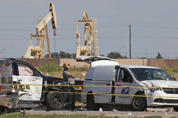 FILE - In this Sunday, Sept. 1, 2019, file photo, law enforcement officials process the crime scene from Saturday's shooting which ended with the shooter, Seth Ator, being shot dead by police in a stolen mail van, right, in Odessa, Texas. The mass shooting in West Texas spread terror over more than 10 miles (16 kilometers) as Ator, fired from behind the wheel of a car. Ator zigzagged through Midland and Odessa, two closely intertwined cities now brought closer by tragedy. (AP Photo/Sue Ogrocki, File)