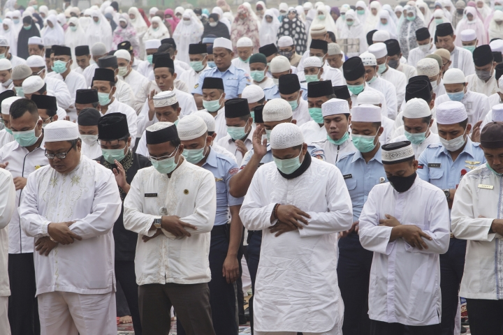 Muslims clasp their arms as they pray for rain in Pekanbaru, Riau province, Indonesia, Wednesday, Sept. 11, 2019. Authorities shut most schools in parts of Indonesia's Sumatra island to protect children from a thick, noxious haze as deliberately set fires burned through peatland forests, officials said Wednesday. (AP Photo)