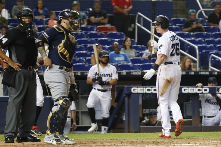Miami Marlins' Garrett Cooper (26) argues a call with home plate umpire Kerwin Danley, left, after striking out, as Milwaukee Brewers catcher Yasmani Grandal, center, stands at the top of the dugout during the eighth inning of a baseball game Tuesday, Sept. 10, 2019, in Miami. The Brewers won 4-3. (AP Photo/Wilfredo Lee)