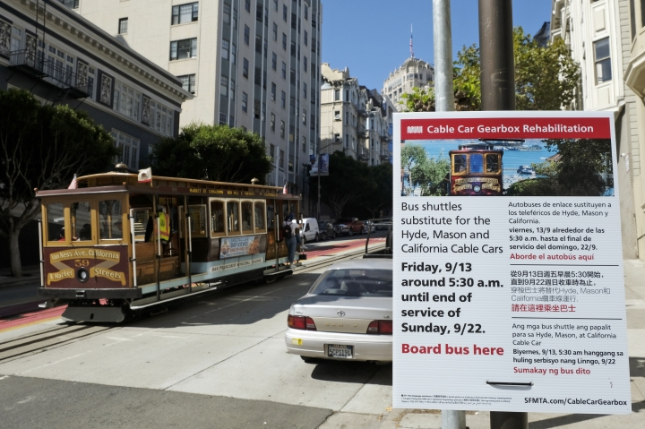 A cable car climbs California Street to Nob Hill past a sign announcing an upcoming rehabilitation project Wednesday, Sept. 11, 2019, in San Francisco. San Francisco's iconic cable cars will stop running for 10 days starting Friday to undergo repairs. The city's transit agency says it needs to get the manually operated cable cars off the street to rehabilitate the gearboxes that power the system that started in the 1890s. Shuttle buses will instead transport people along the steep streets of the cable car routes. (AP Photo/Eric Risberg)
