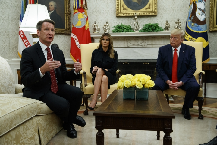 President Donald Trump and first lady Melania Trump listen as acting FDA Commissioner Ned Sharpless talks about a plan to ban most flavored e-cigarettes, in the Oval Office of the White House, Wednesday, Sept. 11, 2019, in Washington. (AP Photo/Evan Vucci)