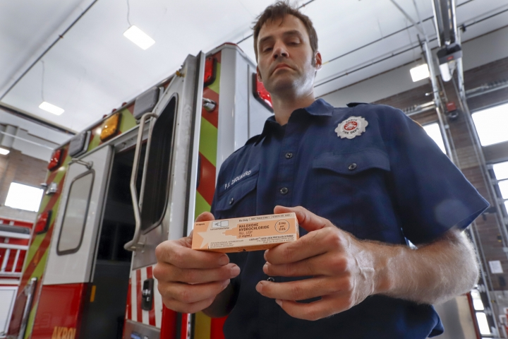 In this Sept. 11, 2019, photo, Akron fire medic Paul Drouhard shows a box containing naloxone that is carried in all the department's emergency vehicles. The drug commonly called Narcan is used primarily to treat narcotic overdoses. The tentative settlement involving the opioid crisis and the maker of OxyContin, Purdue Pharma, could mean that thousands of local governments will one day be paid back for some of the costs of responding to the epidemic. (AP Photo/Keith Srakocic)