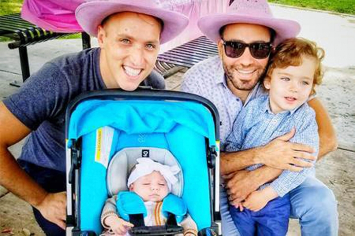 This undated photo provided by Immigration Equality shows Roee, left, and Adiel Kiviti, right, with their children newborn, Kessem and older brother Lev. The Maryland couple is suing to challenge the State Department's refusal to recognize the U.S. citizenship of their infant daughter, who was born in Canada to a surrogate mother this year. (Courtesy of Adiel and Roee Kiviti/Immigration Equality via AP)