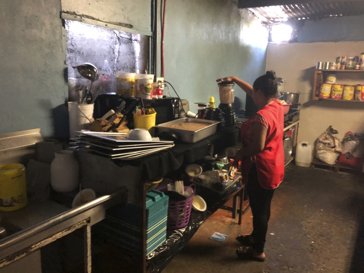 Honduran migrant Dunea Romero, 31, helps helps make Honduran style nachos at the migrant shelter where she is living in Tijuana, Mexico, as she waits for her next asylum hearing in the U.S., Thursday, Sept. 12, 2019, on the border with San Diego. Romero, who was married to a powerful gang leader, grabbed passports for herself and two boys, ages 7 and 11, packed a bag and left the morning after a friend told her that her ex-husband had a hit out on her life. (AP Photo/Julie Watson)