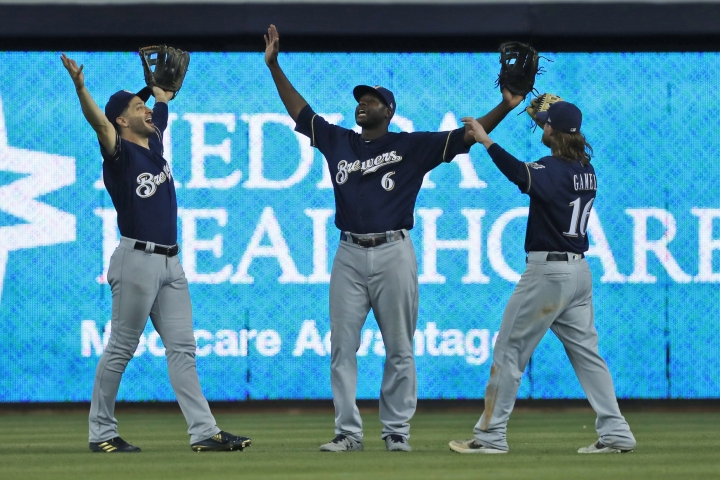 Milwaukee Brewers' Ryan Braun, left, Lorenzo Cain (6) and Ben Gamel (16) celebrate after they defeated the Miami Marlin during a baseball game, Thursday, Sept. 12, 2019, in Miami. (AP Photo/Wilfredo Lee)