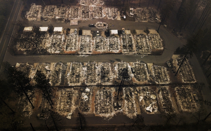 FILE - This Nov. 15, 2018, aerial file photo shows the remains of residences leveled by the Camp wildfire in Paradise, Calif. Pacific Gas & Electric and a group of insurers say they have reached an $11 billion settlement to cover most of the claims from the 2017 and 2018 wildfires in California. The utility said in a statement Friday, Sept. 13, that the tentative agreement covers 85% of the insurance claims, including a fire that decimated the town of Paradise. (AP Photo/Noah Berger, File)