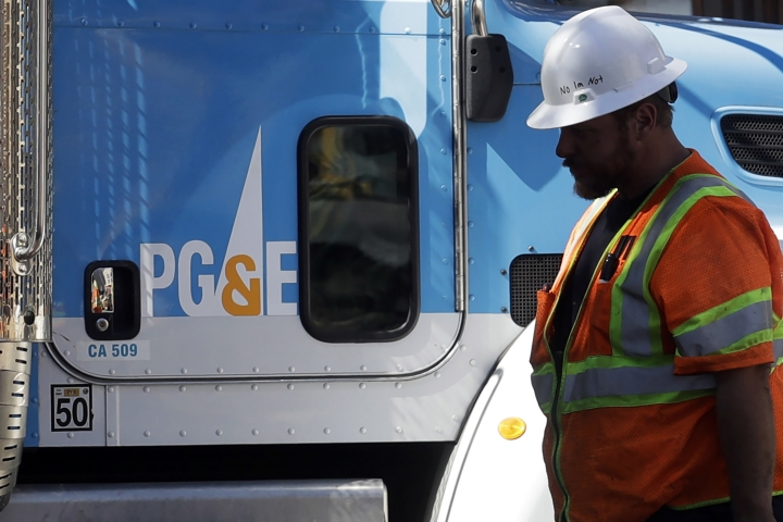 FILE - In this Aug. 15, 2019, file photo, a Pacific Gas & Electric worker walks in front of a truck in San Francisco. Pacific Gas & Electric and a group of insurers say they have reached an $11 billion settlement to cover most of the claims from the 2017 and 2018 wildfires in California. The utility said in a statement Friday, Sept. 13, that the tentative agreement covers 85% of the insurance claims, including a fire that decimated the town of Paradise. (AP Photo/Jeff Chiu, File)