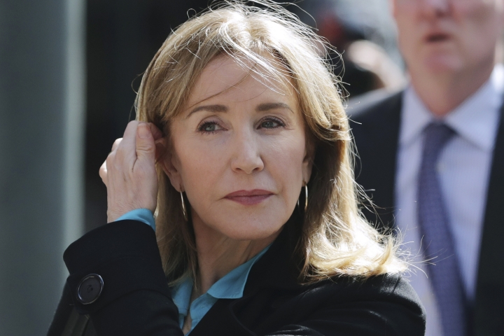 FILE - In this April 3, 2019 file photo, actress Felicity Huffman arrives at federal court in Boston to face charges in a nationwide college admissions bribery scandal. Huffman, who pleaded guilty to a single count of conspiracy and fraud in May, is returning for sentencing in federal on Friday, Sept. 13, 2019 court in Boston. (AP Photo/Charles Krupa, File)