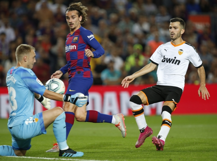 Valencia's goalkeeper Jasper Cillessen makes a save ahead of Barcelona's Antoine Griezmann, centre, during the Spanish La Liga soccer match between FC Barcelona and Valencia CF at the Camp Nou stadium in Barcelona, Spain, Saturday, Sep. 14, 2019. (AP Photo/Joan Monfort)