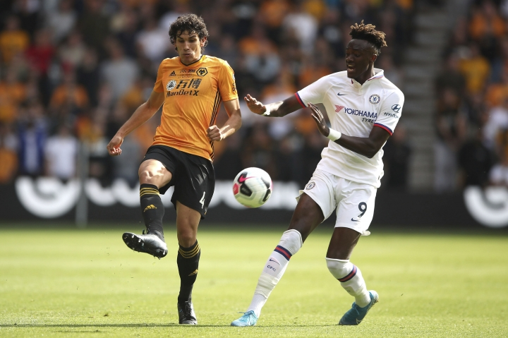 Wolverhampton Wanderers' Jesus Vallejo, left, and Chelsea's Tammy Abraham battle for the ball during their English Premier League soccer match at Molineux, Wolverhampton, England, Saturday, Sept. 14, 2019. (Nick Potts/PA via AP)