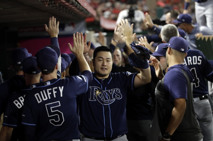 Tampa Bay Rays' Ji-Man Choi is high-fived in the dugout after scoring on a double by Travis d'Arnaud during the sixth inning of a baseball game against the Los Angeles Angels, Saturday, Sept. 14, 2019, in Anaheim, Calif. (AP Photo/Marcio Jose Sanchez)