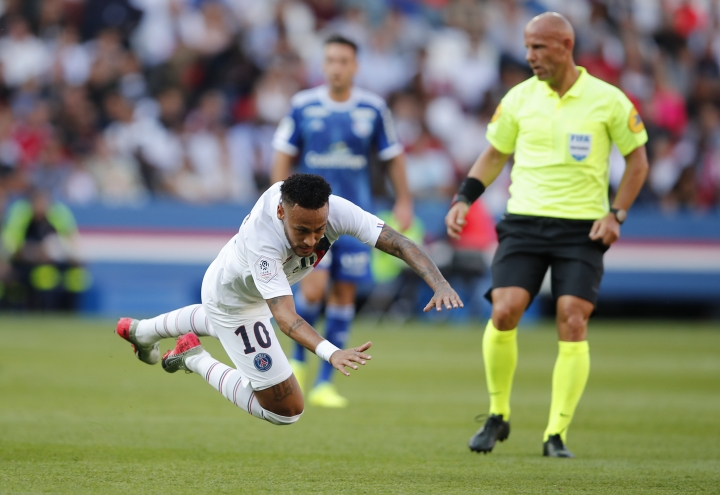 PSG's Neymar is airborne after he was tackled by Strasbourg's Mohamed Simakan during the French League One soccer match between Paris Saint Germain and Strasbourg at the Parc des Princes Stadium in Paris, France, Saturday Sept.14, 2019. (AP Photo/Francois Mori)