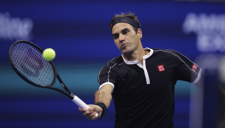 Roger Federer, of Switzerland, returns to Grigor Dimitrov, of Bulgaria, during the quarterfinals of the U.S. Open tennis tournament Tuesday, Sept. 3, 2019, in New York. (AP Photo/Charles Krupa)