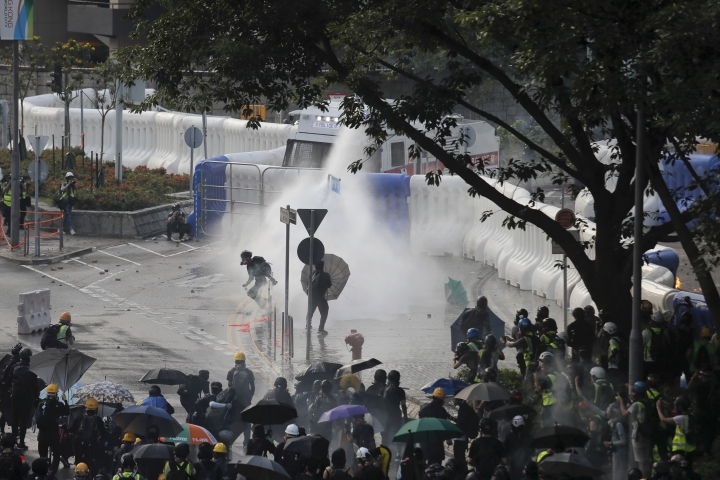 Anti-government protesters are sprayed by water cannon during a demonstration near Central Government Complex in Hong Kong, Sunday, Sept. 15, 2019. Police fired a water cannon and tear gas at protesters who lobbed Molotov cocktails outside the Hong Kong government office complex Sunday, as violence flared anew after thousands of pro-democracy supporters marched through downtown in defiance of a police ban. (AP Photo/Kin Cheung)