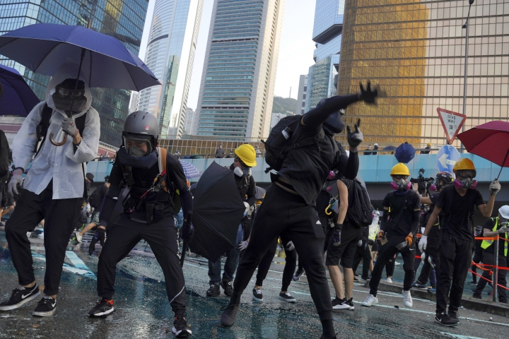 An anti-government protester throws a rock near Central Government Complex in Hong Kong, Sunday, Sept. 15, 2019. Police fired a water cannon and tear gas at protesters who lobbed Molotov cocktails outside the Hong Kong government office complex Sunday, as violence flared anew after thousands of pro-democracy supporters marched through downtown in defiance of a police ban. (AP Photo/Vincent Yu)