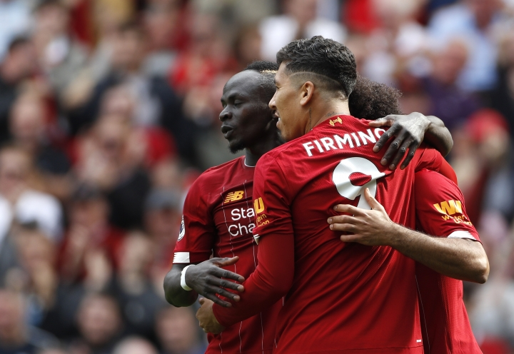 Liverpool's Sadio Mane, left, celebrates with Liverpool's Roberto Firmino, center, and Liverpool's Mohamed Salah, right, after scoring his sides second goal during the English Premier League soccer match between Liverpool and Newcastle at Anfield stadium in Liverpool, England, Saturday, Sept. 14, 2019. (AP Photo/Rui Vieira)