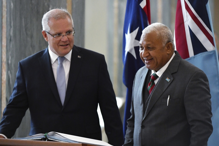 Australia's Prime Minister Scott Morrison, left, watches as Fiji's Prime Minister Voreqe Bainimarama signs the visitors book after an official welcome ceremony at Parliament House in Canberra, Monday, Sept. 16, 2019. (Mick Tsikas/Pool Photo via AP)