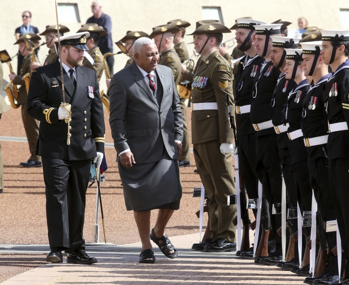 Fiji's Prime Minister Voreqe Bainimarama, center, inspects an honor guard outside Parliament House in Canberra, Australia, during his official welcome to the Australian capital bon Monday, Sept. 16, 2019. Bainimarama visited Canberra on the last days of his Australian visit that started in Sydney on Thursday. (AP Photo/Rod McGuirk)