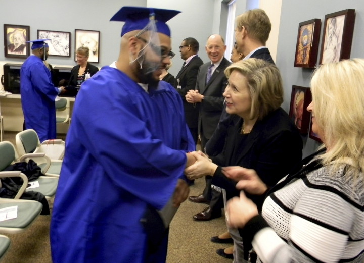 FILE - In this March 28, 2019 file photo, Minnesota first lady Gwen Walz, center, greets an inmate during a high school and college graduation ceremony at the Minnesota Correctional Facility - Stillwater in Bayport, Minn. A deleted video from a forum that turned tense over race demonstrates some of the risks in Minnesota in first lady Gwen Walz's push for criminal justice reform. Minnesota Public Radio reports that a forum at Twin Cities Public Television one day last May, which included screenings of clips from the documentary, turned tense when the moderator pressed participants about race. A top aide to Democratic Gov. Tim Walz then sought to make sure a video of the forum didn't circulate. (Josh Verges/Pioneer Press via AP, File)