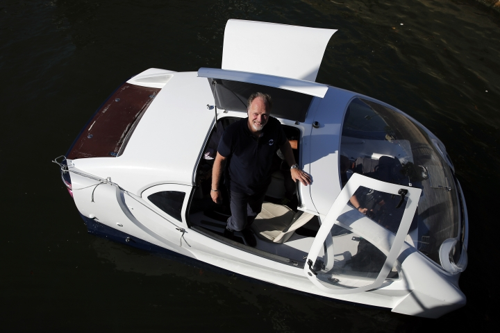 In this photo taken Tuesday Sept. 17, 2019, SeaBubbles co-founder Anders Bringdal poses aboard an hydrofoil boat SeaBubble on the Seine river in Paris. Paris is testing out a new form of travel - an eco-friendly bubble-shaped taxi that zips along the water, capable of whisking passengers up and down the Seine River. (AP Photo/Francois Mori)