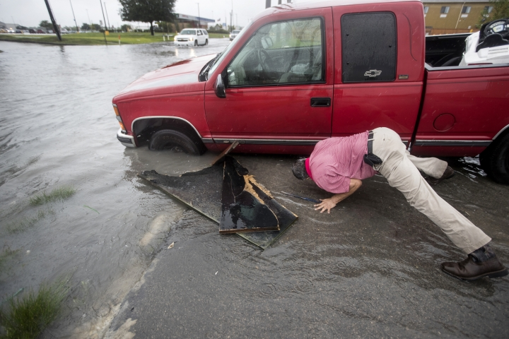 Felipe Morales works on getting his truck out of a ditch filled with high water during a rain storm stemming from rain bands spawned by Tropical Storm Imelda on Tuesday, Sept. 17, 2019, in Houston. He was able to get help when a man with a truck helped pull him from the ditch. (Brett Coomer/Houston Chronicle via AP)