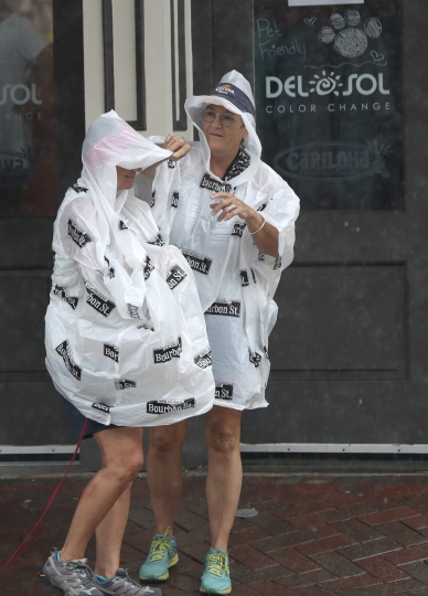 Linda Orndorff, right, adjusts the hood of Candy Lester's rain poncho as they explore The Strand in Galveston, Texas on Tuesday, Sept. 17, 2019. The two, from Florida, were trying to make the best of the rainy weather. Heavy rain from Tropical Storm Imelda is expected to soak Galveston County and could cause flooding. (Jennifer Reynolds/The Galveston County Daily News via AP)